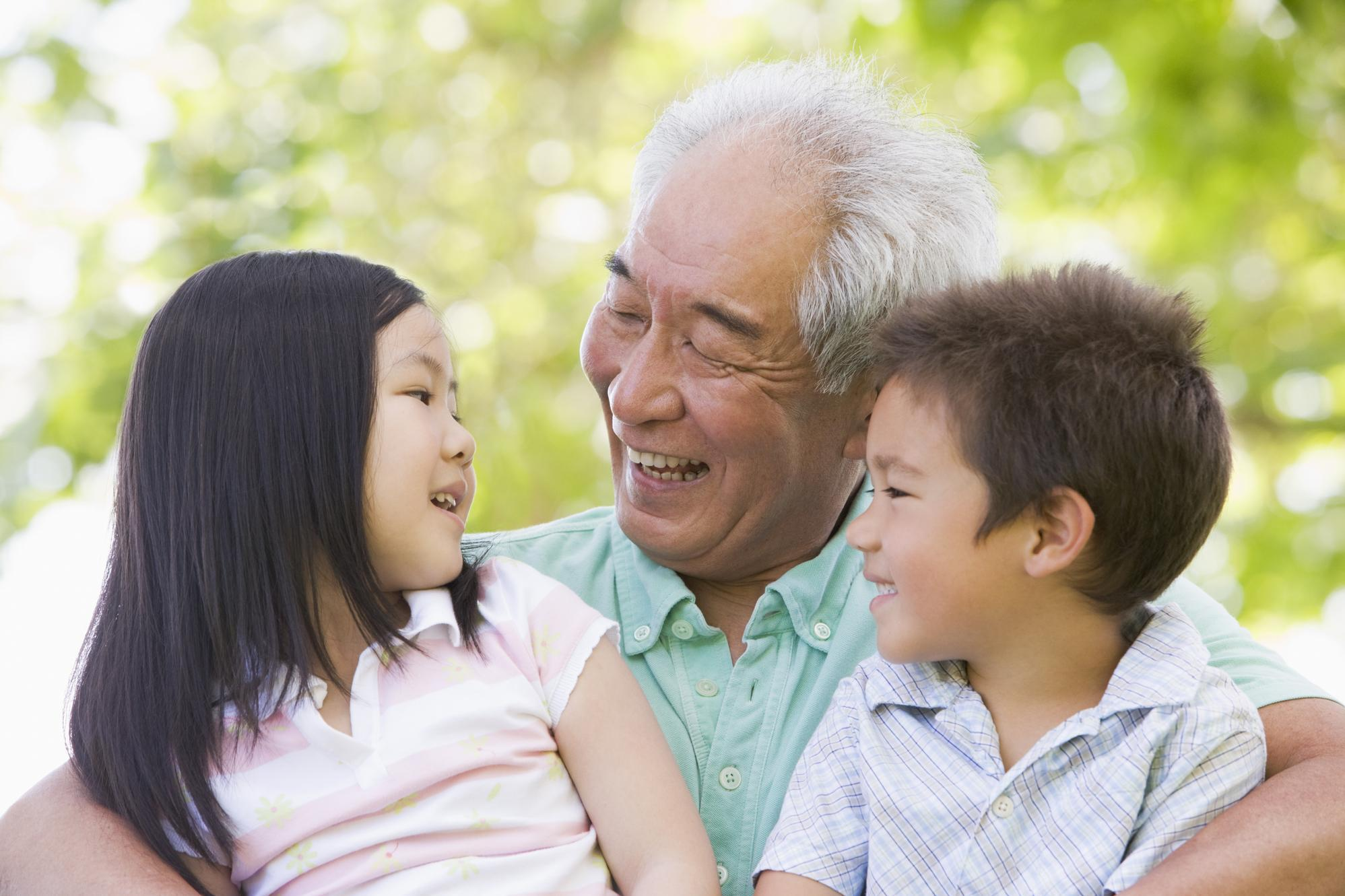 Grandfather laughing and visiting with grandchildren